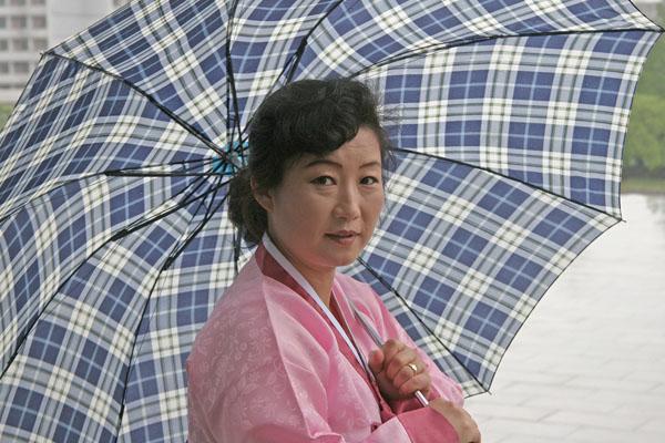 mulher-norte-coreana-segurando-um-guarda-chuva-azul